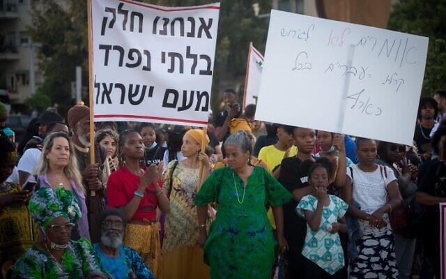 Des membres de la communauté des Hébreux israélites de la ville méridionale de Dimona protestent contre les ordres d'expulsion remis à certains de leurs membres, sur la place Habima, à Tel Aviv, le 1er juin 2021. La bannière indique : «Nous faisons partie intégrante du peuple d'Israël.» (Crédit : Miriam Alster/Flash90)