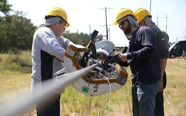Des ouvriers installent le robot Bombyx de Facebook qui se déplace le long des lignes électriques, les enveloppant de câbles en fibre optique, afin de déployer l'Internet en fibre optique dans les communautés. (Facebook)