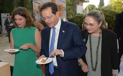 Avec à sa droite son épouse Michal et à sa gauche la ministre de la Protection environnementale Tamar Zandberg, le président Isaac Herzog goûte du poulet fabriqué à partie de cellules cultivées en laboratoire à la résidence du président de Jérusalem, le 25 octobre 2021. (Crédit : Amos Ben Gershom/ GPO)