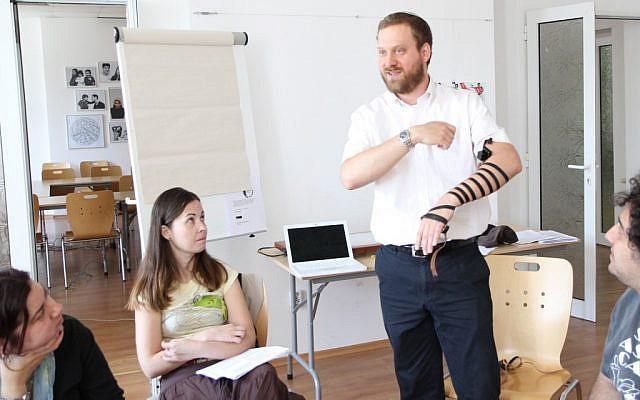 Le Rabbin Josh Ahrens qui montre comment mettre les téfilin lors d'un cours de conversion à Sofia, en Bulgarie (Crédit : Dianna Cahn/JTA)