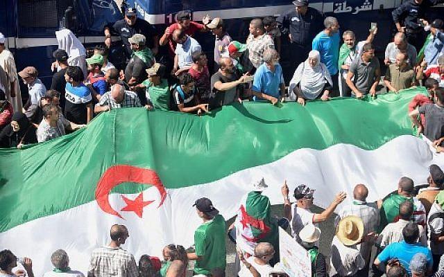 Les manifestants défilent avec un drapeau national lors d'une manifestation contre la classe dirigeante à Alger, la capitale algérienne, le 30 août 2019, pour la vingt-huitième vendredi consécutive et pour marquer le sixième mois écoulé depuis le début du mouvement. Photo : RYAD KRAMDI / AFP