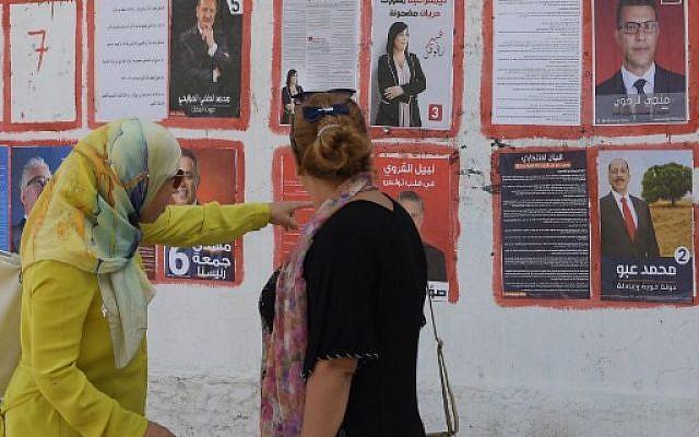 Les femmes tunisiennes regardent les affiches des candidates à la présidence dans la capitale, Tunis le 9 septembre 2019. La Tunisie a longtemps été considérée comme une pionnière des droits des femmes dans le monde arabe, mais à la veille des élections présidentielles, les femmes remettent en question cette réputation. Activistes passionnées, femmes laïques ou anciennes élues, de nombreuses femmes affirment ne pas attendre «grand chose» des sondages qui commencent avec le premier tour de scrutin le 15 septembre. Photo : Fethi Belaid / AFP