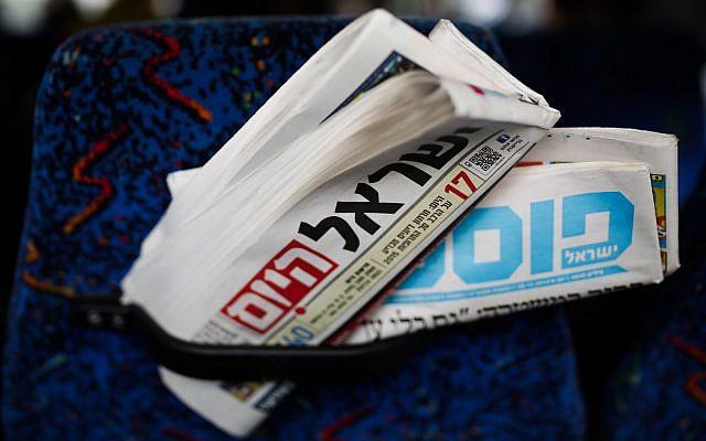 """Illustration de journaux israéliens, """"Israel Hayom"""" et """"Israel Post"""" à l'intérieur d'un bus, 28 décembre 2014. Photo : Maxim Dinshtein / Flash90"""
