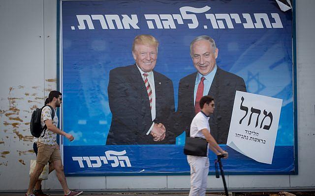 Des Israéliens passent devant un panneau d'affichage représentant le président américain Donald Trump avec le Premier ministre israélien Benjamin Netanyahu, dans le cadre de la campagne électorale du Likoud, à Tel-Aviv le 11 septembre 2019. Photo : Miriam Alster / Flash90