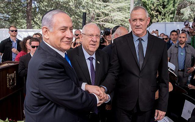 Le président Reuven Rivlin, le Premier ministre Benjamin Netanyahu et le dirigeant bleu et blanc Benny Gantz se serrent la main lors de la cérémonie commémorative du défunt président Shimon Peres au cimetière Mount Herzl à Jérusalem le 19 septembre 2019. Photo : Yonatan Sindel / Flash90