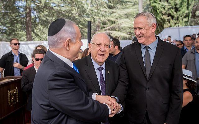 Le président Reuven Rivlin, le Premier ministre Benjamin Netanyahu et le dirigeant du parti Bleu et Blanc, Benny Gantz, se serrant la main lors de la cérémonie commémorative du défunt président Shimon Peres au cimetière du Mont Herzl à Jérusalem le 19 septembre 2019. Photo : Yonatan Sindel / Flash90