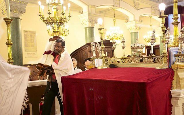 Guershon Nduwa portant la Torah lors d'une cérémonie religieuse. Crédit : Guershon Nduwa