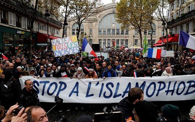 """Manifestants agitant des drapeaux français, chantent des slogans et tenant des pancartes avec des messages tels que """"Stop à tous les types de racisme"""" et """"Stop à l'islamophobie"""" lors de la manifestation contre l'islamophobie devant la gare du Nord, à Paris, le 10 novembre 2019. GEOFFROY VAN DER HASSELT / AFP"""