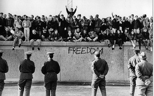 Berlin, Allemagne, Allemagne - En novembre 1989, des étudiants est-allemands sont assis au sommet du mur de Berlin, à la porte de Brandebourg, en face des gardes-frontières. La destruction du mur jadis haï a marqué la fin d'une Allemagne divisée - University of Minnesota Institute of Advanced Studies