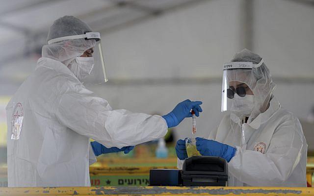 Les membres de l'équipe médicale de Magen David Adom, portant un équipement de protection, manipulent un échantillon de test de coronavirus sur un site de drive-in pour la collecte d'échantillons de test de coronavirus, à Tel Aviv, le 20 mars 2020. Photo de Gili Yaari / Flash90