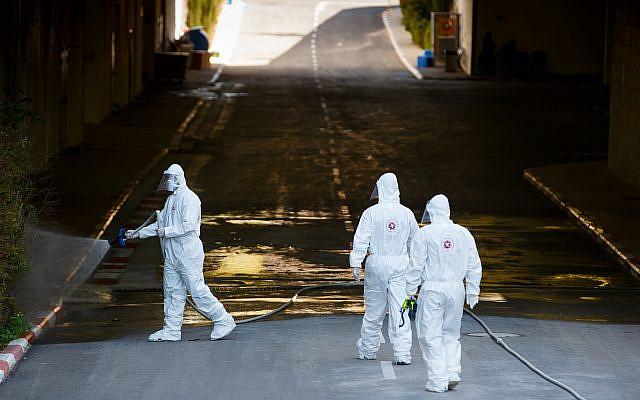 Des pompiers israéliens portant des vêtements de protection, désinfectent l'hôpital d'Assuta à Ashdod, le 22 mars 2020, dans le cadre de mesures visant à empêcher la propagation du coronavirus. Photo de Flash90