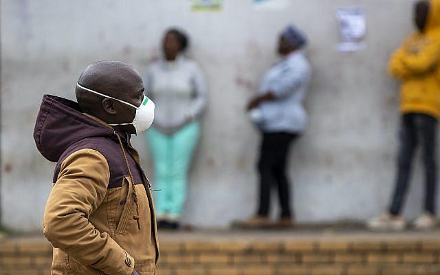 Un homme portant des masques pour se protéger contre le coronavirus, passe devant des personnes faisant la queue pour faire du shopping à Duduza, à l'est de Johannesburg, en Afrique du Sud, le jeudi 2 avril 2020. (Photo AP / Themba Hadebe)