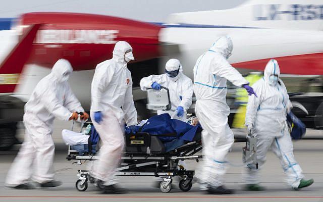 Un patient français gravement malade du coronavirus est transporté depuis un avion ambulancier après son atterrissage à l'aéroport international de Dresde, en Allemagne, le samedi 4 avril 2020. (Robert Michael / dpa via AP)