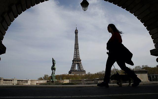 Une femme promenant son chien sur un pont de Paris, avec la tour Eiffel vue en arrière-plan, lors du confinement à l'échelle nationale pour contrer le COVID-19, le mardi 7 avril 2020. (Photo AP / Christophe Ena)