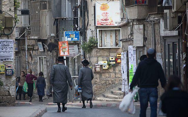 Des juifs ultra orthodoxes marchant dans le quartier ultra orthodoxe de Meah Shearim, Jérusalem, le 25 mars 2020. Photo de Yonatan Sindel / Flash90