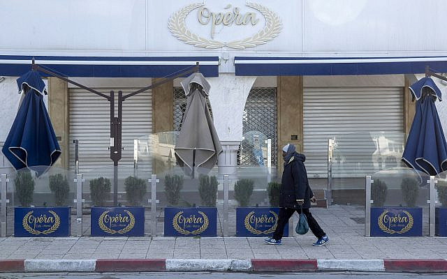 Un homme passant devant un café fermé à La Marsa, à l'extérieur de Tunis, le jeudi 26 mars 2020. (Photo AP / Hassene Dridi)