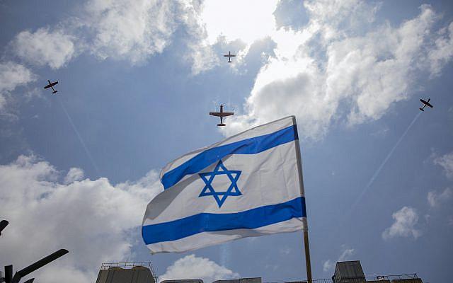 Drapeau israélien flottant alors qu'une équipe de voltige de l'Armée de l'Air vole en formation au-dessus du centre médical Hillel Yaffe, lors du confinement à la suite de mesures gouvernementales visant à empêcher la propagation du coronavirus, le 72e jour de l'indépendance d'Israël, dans la ville israélienne de Hadera, dans le nord d'Israël. Israël, mercredi 29 avril 2020. (Photo AP / Ariel Schalit)