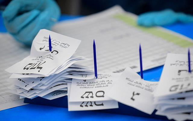 Les Israéliens comptant les bulletins de vote restants des Israéliens placés en quarantaine à domicile après leur retour des zones infectées par le coronavirus, dans une tente dans l'entrepôt du comité central des élections à Shoham, le 4 mars 2020. Photo de Flash90