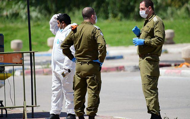 Personnel israélien du Magen David Adom et des soldats israéliens à une station de débarquement pour les résidents de la ville ultra orthodoxe de Bnei Brak qui ont été infectés par le coronavirus, et en voie de mise en quarantaine d'hôtels, près du centre commercial Ayalon le 3 avril 2020. . Photo de Tomer Neuberg / Flash90
