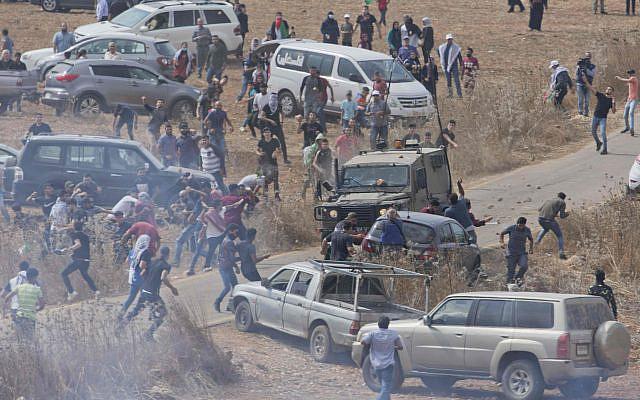 Des manifestants palestiniens lançant des pierres sur un véhicule de l'armée israélienne lors d'affrontements dans le village de Tormusayya, au nord-est de Ramallah, en Judée-Samarie, le jeudi 17 octobre 2019. (Photo AP / Nasser Nasser)