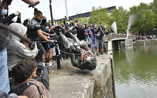 Les manifestants jetant une statue du marchand d'esclaves Edward Colston dans le port de Bristol, lors d'un rassemblement de protestation Black Lives Matter, à Bristol, Angleterre, le dimanche 7 juin 2020. (Ben Birchall / PA via AP)