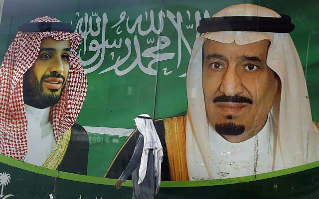 Sur cette photo d'archive du 7 mars 2020, un homme passant devant une banderole montrant le roi saoudien Salmane, à droite, et son prince héritier Mohammed ben Salmane, à l'extérieur d'un centre commercial à Jiddah, en Arabie saoudite. (Photo AP / Amr Nabil, fichier)