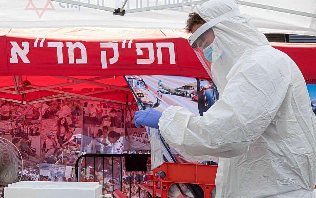 Un travailleur médical de Magen David Adom testant des Israéliens sur un site de drive-in pour collecter des échantillons pour les tests de coronavirus le 10 juillet 2020. Photo de Chen Leopold / Flash90