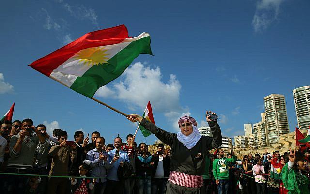 Dans cette photo d'archive du 21 mars 2016, la jeune fille kurde syrienne de Nazdan, qui a fui son domicile à Qamishli, en Syrie, portant des vêtements traditionnels, dansant et agitant un drapeau kurde, lors d'une célébration de la journée Nowruz, à Beyrouth, au Liban . (Photo AP / Bilal Hussein, dossier)