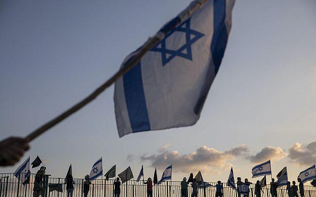 Des manifestants israéliens tenant des drapeaux israéliens se tenant sur un pont pour manifester contre le Premier ministre israélien Benjamin Netanyahu et son gouvernement pendant les vacances de Souccot à Hefer Valley, en Israël, dimanche 4 octobre 2020. (Photo AP / Ariel Schalit)