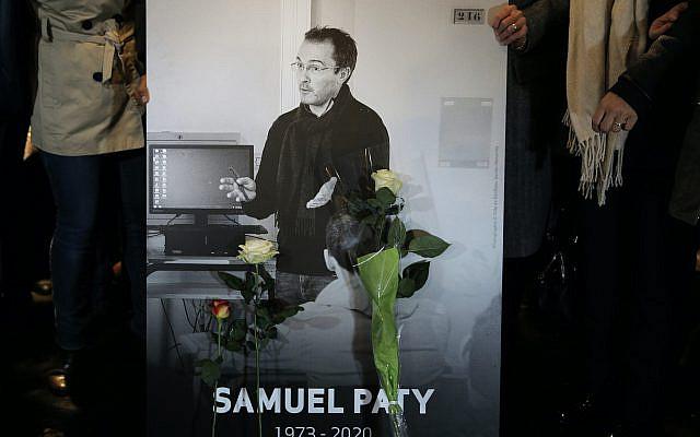 Photo du professeur d'histoire Samuel Paty, décapité la semaine dernière, lors d'une marche commémorative en son hommage, mardi 20 octobre 2020 à Conflans-Sainte-Honorine, au nord-ouest de Paris. (Photo AP / Lewis Joly)