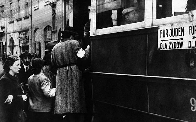 """Une scène dans le ghetto où des Juifs portent des brassards blancs ornés de l'étoile de David et des tramways marqués des mots """"Pour les Juifs seulement"""", à Cracovie, Pologne, le 1er février 1941. (Photo AP)"""