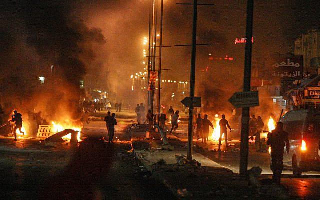 Des manifestants jettant des pierres lors d'affrontements avec la police anti-émeute près d'un bureau des impôts à Ettadhamen, Tunisie, à 5 km de Tunis, le vendredi 10 janvier 2014. Des affrontements ont éclaté à Ettadhamen, près de Tunis, vendredi soir entre la police et les manifestants. le mécontentement monte sur les nouvelles taxes levées par le gouvernement vendredi soir (AP / Aimen Zine)