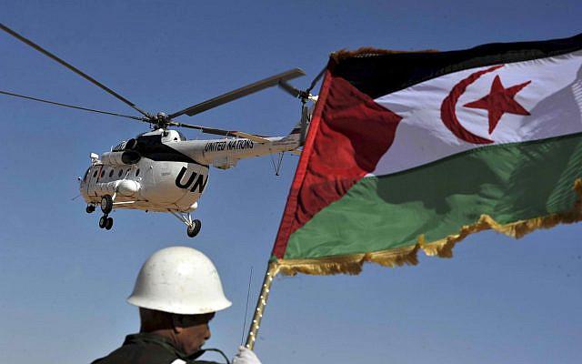 Un soldat tenant le drapeau du Front Polisario alors qu'un hélicoptère des Nations Unies file au-dessus du camp de réfugiés de Smara près de Tindouf, dans le sud-ouest de l'Algérie, le samedi 5 mars 2016. (Photo AP / Toufik Doudou)