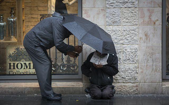Un homme donnant de l'argent à un sans-abri dans la rue Jaffa, au centre-ville de Jérusalem, le 3 novembre 2014. Photo de Yonatan Sindel / Flash90