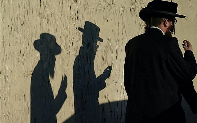 Des hommes passant devant le Yetev Lev le lundi 23 novembre 2020, dans le quartier de Brooklyn à New York. (Photo AP / Frank Franklin II)