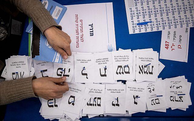 Les travailleurs de la Commission électorale centrale comptent les bulletins de vote restants au parlement israélien à Jérusalem, après les élections générales, le 25 mars 2020. Photo de Yonatan Sindel / Flash90
