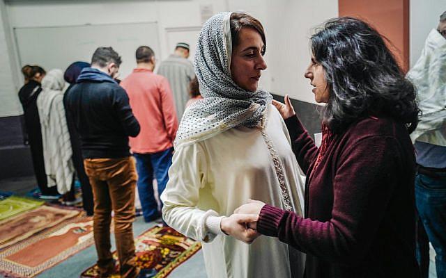 L'Imam française Kahina Bahloul s'entretient avec un ami après avoir dirigé une prière du vendredi dans une salle louée du 11e arrondissement de Paris, le 21 février 2020. (Crédit : LUCAS BARIOULET / AFP)