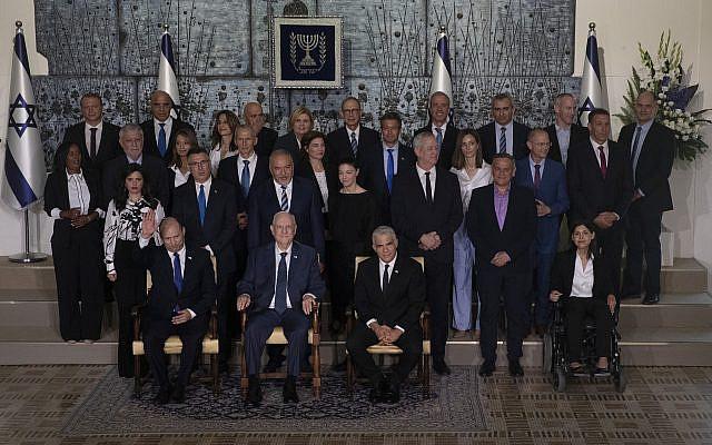 Le Premier ministre israélien Naftali Bennett, assis à gauche, le président Reuven Rivlin, assis au centre, et le Premier ministre adjoint et ministre des Affaires étrangères Yair Lapid assis à droite, posent pour la photo de groupe avec les ministres du nouveau gouvernement à la résidence du président à Jérusalem, lundi 14 juin 2021. (AP Photo/Maya Alleruzzo)