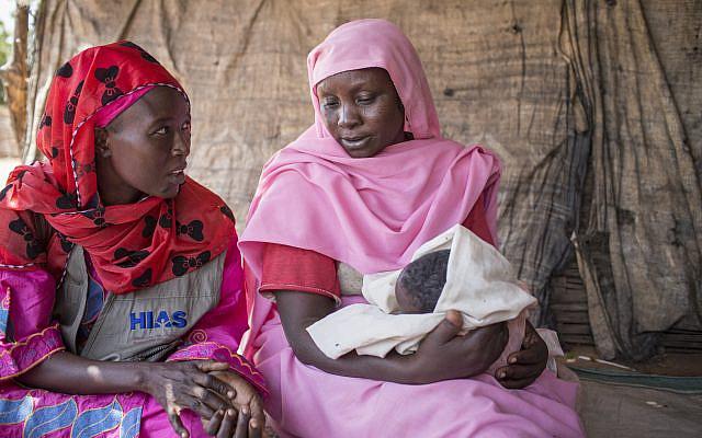 Tchad/Réfugiés du Darfour - Une volontaire communautaire de HIAS rencontre Amneh Yakum Abbakah, 40 ans, qui a appris à fabriquer des paniers grâce aux activités de HIAS et gère maintenant sa propre boutique avec les revenus qu'elle a générés en les vendant. Le 6 novembre 2013 - Photo par Glenna Gordon