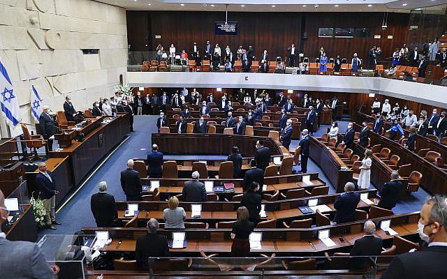 Les législateurs israéliens se tenant dans le plénum de la Knesset lors de la cérémonie de prestation de serment du 24e gouvernement israélien, à la Knesset, ou parlement, à Jérusalem, le mardi 6 avril 2021. (Alex Kolomoisky/POOL via AP)