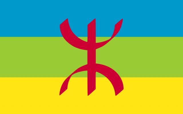 Le « Drapeau berbère ». Crée initialement par l'Académie berbère (Agraw Imazighen) dans les années 1970, le drapeau est adopté en 1998 comme drapeau des Berbères par le Congrès mondial amazigh (CMA, Agraw Amadlan Amazigh). Il est représenté par un Yaz rouge, couleur représentant le teint brun des populations berbères, sur un fond tricolore horizontal bleu, vert et jaune. Le bleu représente le ciel, le vert représente le reflet des montagnes sur l'eau, et le jaune représente le sable de la mer.