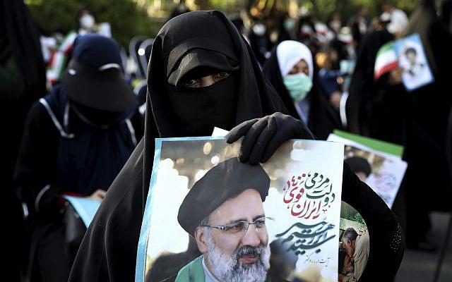 Photo d'archive du 16 juin 2021, des partisans du candidat à la présidentielle Ebrahim Raisi tenant sa photo lors d'un rassemblement à Téhéran, en Iran.. (AP Photo/Ebrahim Noroozi, Dossier)
