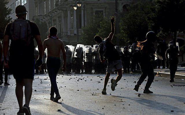 Des manifestants anti-gouvernementaux jettent des pierres sur la police anti-émeute lors d'une manifestation marquant le premier anniversaire de l'explosion massive dans le port de Beyrouth, près de la place du Parlement, à Beyrouth, au Liban, le mercredi 8 août. 4, 2021. Unis dans le chagrin et la colère, les familles des victimes et d'autres Libanais sont descendus dans les rues de Beyrouth mercredi pour exiger des comptes alors que les banques, les entreprises et les bureaux du gouvernement fermaient pour marquer l'année depuis explosion. (Photo AP / Bilal Hussein)