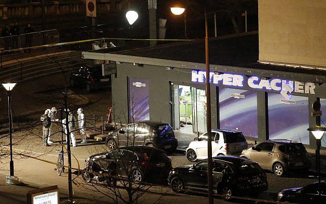 DOSSIER - Photo d'archive du vendredi 9 janvier 2015, des policiers travaillent sur les lieux de l'Hypercacher à Paris après la prise d'otages par le terroriste Amedy Coulibaly.  (AP Photo/François Mori, dossier)