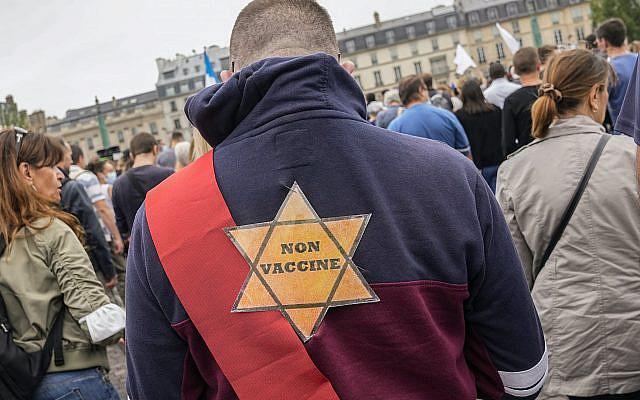 """Une étoile jaune avec écrit """"non vacciné"""" au dos d'un manifestant anti-vaccin lors d'un rassemblement à Paris, le samedi 17 juillet 2021. (AP Photo/Michel Euler, Dossier)"""