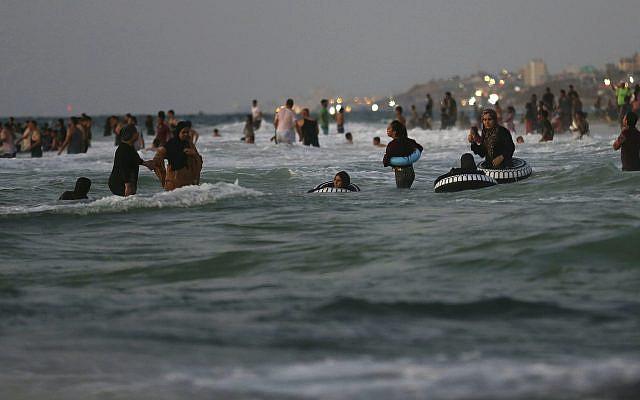 Des Palestiniens nageant dans la mer Méditerranée au coucher du soleil, sur la plage du camp de réfugiés de Deir el-Balah, dans le centre de la bande de Gaza, le vendredi 20 août 2021. (AP Photo/Adel Hana)