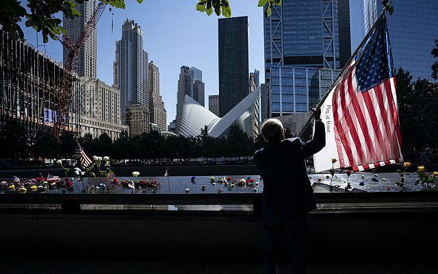 Germano Rivera tenant un drapeau lors des cérémonies commémorant le 20e anniversaire des attentats terroristes du 11 septembre 2001, le samedi 11 septembre 2021, au National September 11 Memorial & Museum à New York. (Photo AP/John Minchillo)