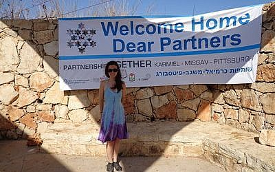 Abby Gordon stands in front of a banner welcoming Pittsburgh's Partnership 2gether partners to Mt. Arbel in the Misgav Region