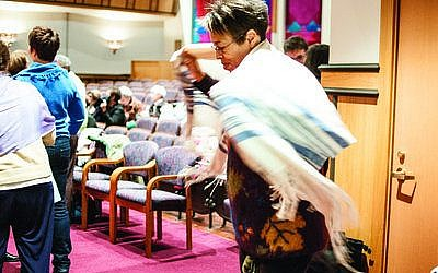 "Esther Chaya Batsarah of Swissvale wraps herself in a tallit, Sunday, Oct. 28, at Rodef Shalom Congregation before she and more than 100 others protest the arrest of Anat Hoffman at a ""Shema-in."" Hoffman was arrested Oct. 16 for reciting the Shema at the Western Wall in Jerusalem. Female attendees at the Shema-in wore tallitot to support Hoffman and her organization, Women at the Wall. (Chronicle photos by Lindsay Dill)"