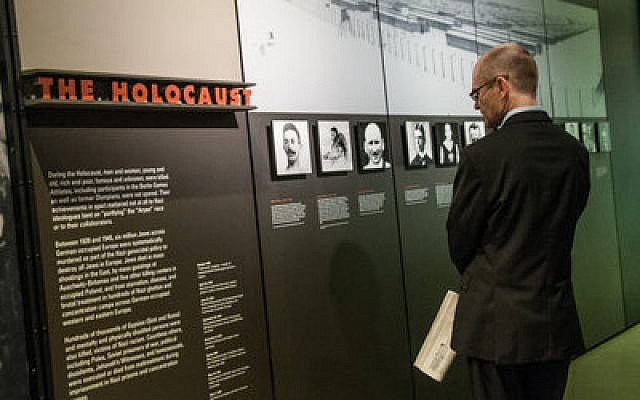 "Bernd Georg Reindl, German consul for political and scientific development, walks through the premier of the August Wilson Center's ""Nazi Olympics"" exhibit, Monday, Oct. 15. The event is the first in a series of collaborations between the African-American and Jewish communities in Pittsburgh. (Chronicle photo by Lindsay Dill)"